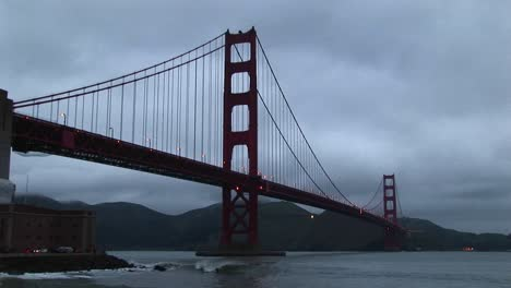 Surf-Rolls-Over-Rocks-Under-Historic-Golden-Gate-Bridge-In-San-Francisco-Bay
