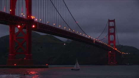 A-Wormseye-View-Of-The-Golden-Gate-Bridge-At-Night-With-Its-Lights-Reflecting-On-The-Water