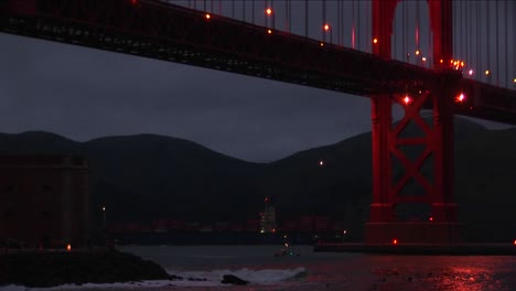 Small-Boats-Passing-Under-The-Golden-Gate-Bridge-At-Night-Are-Dwarfed-By-The-Enormous-Structure