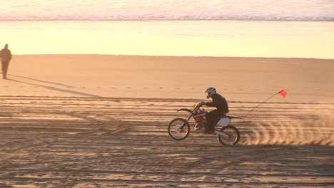A-Dirtbiker-Makes-Tracks-On-A-Sandy-Beach-During-The-Goldenhour