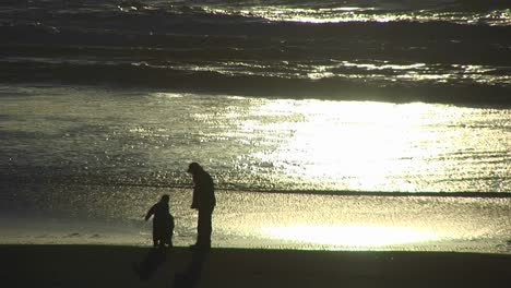 A-Man-And-A-Two-Children-Explore-The-Beach-As-The-Tide-Goes-Out-During-The-Goldenhour
