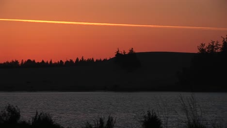 Spectacular-Footage-Of-A-Lake-And-Surrounding-Scenery-Under-An-Orange-Goldenhour-Sky