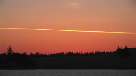 Longshot-Of-The-Vapor-Trail-From-A-Jet-Makes-A-Colorful-Streak-Across-The-Goldenhour-Sky