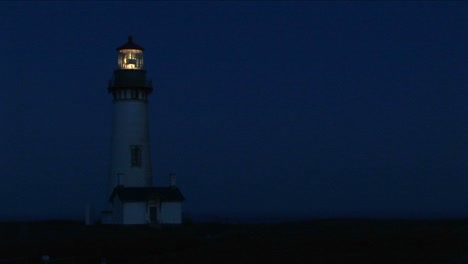 Medium-Shot-Of-Lighthouse-At-Night-With-Its-Bright-Beacon-Signaling-A-Warning-To-Passing-Ships