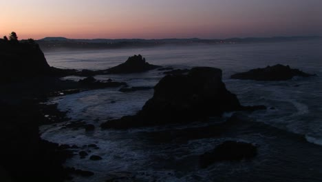 A-Broad-Band-Of-Pink-And-Orange-Sky-Brightens-This-Footage-Of-A-Gray-Rocky-Coastline