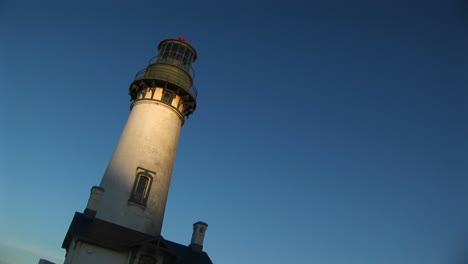 A-Handheld-Jaunty-View-Of-A-Lighthouse-With-Sunlight-On-Its-White-Tower