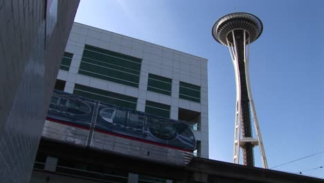 A-Lowangle-View-Of-The-Monorail-Passing-The-Space-Needle-And-Other-Downtown-Seattle-Buildings