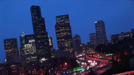 An-Angled-View-Of-Seattle\-S-Downtown-Skyline-At-Night-With-Traffic
