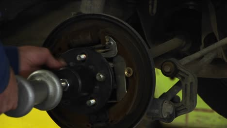 A-Mechanic-Tightens-Bolts-On-A-Wheel-Being-Fastened-To-An-Axle