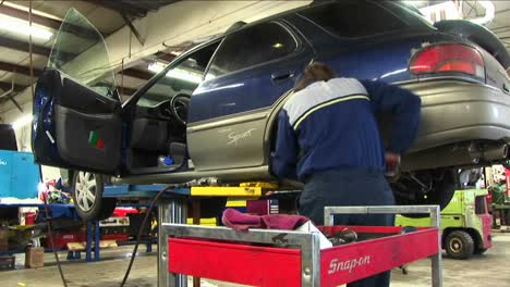 A-Mechanic-Uses-A-Wrench-To-Work-On-The-Wheelmount-Of-An-Auto-On-A-Hydraulic-Lift