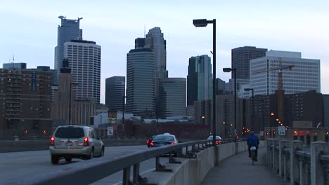 Cars-And-A-Bicyclist-Cross-A-Bridge-Into-The-City
