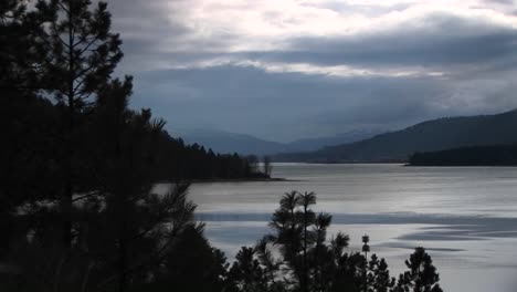 A-Scenic-View-Of-An-Ocean-Inlet-And-Shoreline-With-Trees-And-Hills-In-Grays-And-Blues