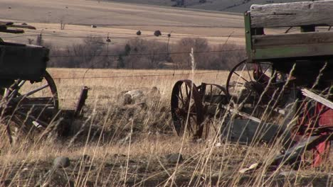 Broken-And-Abandoned-Farm-Machinery-Rest-In-A-Field-That-Overlooks-The-Dry-Prairie-Beyond