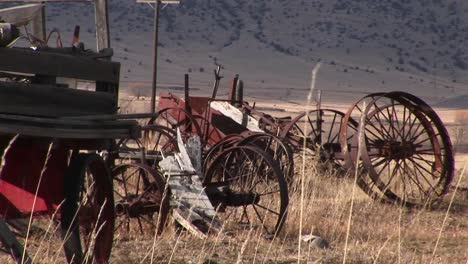 Broken-And-Rusty-Vintage-Wagonwheel-Rims-And-Other-Old-Equipment-Are-Abandoned-In-The-Dry-Prairie-Grass