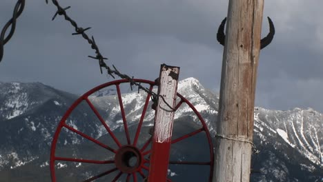 Medium-Shot-Of-Western-Mountains-Red-Wagonwheel-Rim-Barbedwire-And-Cattle-Horns-Tacked-To-A-Pole