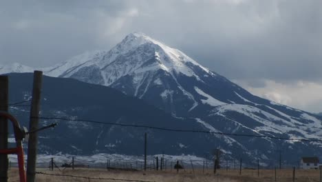 A-Snowcapped-Mountain-Watches-Over-A-Ranch-With-Barbedwire-Fences