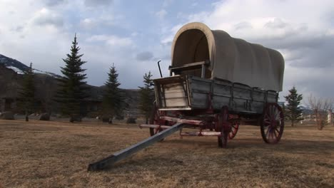 A-Covered-Wagon-Looks-Right-At-Home-Against-The-Backdrop-Of-Evergreens-And-Prairie