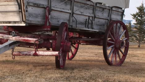 A-Close-Look-At-The-Lower-Half-Of-A-Covered-Wagon-With-Its-Wagon-Wheels-Painted-Red