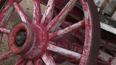 A-Worn-Covered-Wagon-Wheel-Shows-The-Remains-Of-Its-Original-Red-Paint