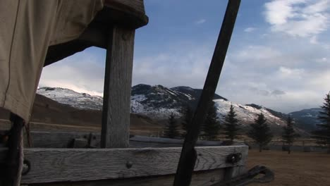 The-Camera-Looks-Through-An-Opening-In-A-Covered-Wagon-For-A-View-Of-The-Mountains-Beyond