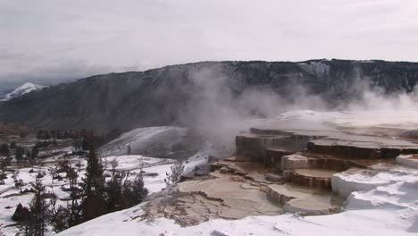 A-Look-At-Hot-Springs-Limestone-Terraces-In-Winter-With-Scenic-Mountains-In-The-Background