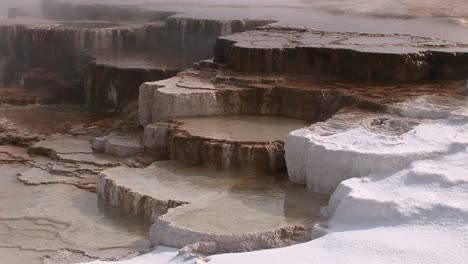 A-Colorful-Closeup-Look-At-A-Hot-Springs-Limestone-Terrace-With-Steam-Snow-And-Thermal-Pool