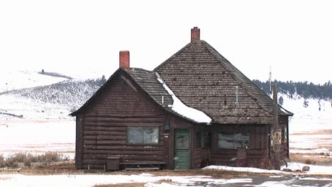 A-Large-Addition-Tacked-On-To-A-Small-Log-Cabin-Mirrors-Its-Steep-Roof-And-Chimney