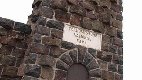 """Camera-Focuses-On-A-Vintage-Yellowstone-National-Park""""""""-Sign-Embedded-In-The-Brick-Facade-Of-An-Old-Building"""""""""""