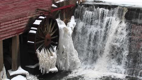A-Closeup-Of-Water-Flowing-Past-A-Gristmill-Whose-Waterwheel-Is-Immobilized-By-Freezing-Temperatures