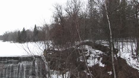 The-Camera-Pans-Left-From-A-Rural-Winter-Landscape-To-Dam-Next-To-A-Mill-With-Waterwheel