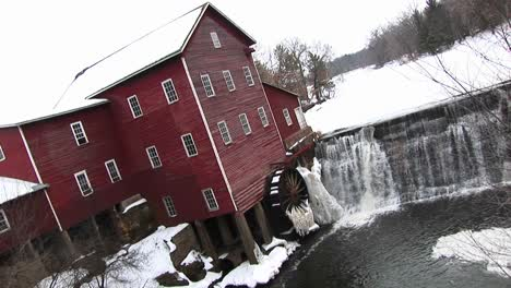 An-Angled-View-Of-A-Mill-With-Waterwheel-And-Dam-In-Winter