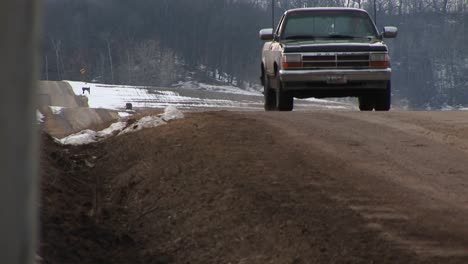 Camera-Placed-In-Roadside-Ditch-Along-A-Rural-Twolane-Road-Captures-A-Pickup-Truck-Coming-Into-View-Over-A-Rise