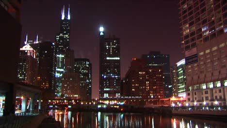 A-Commuter-Train-Moves-Slowly-Across-The-Brilliant-Chicago-Skyline-At-Night