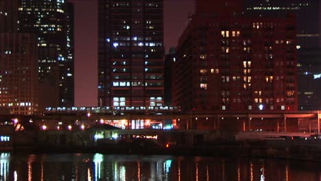 An-Elevated-Commuter-Train-Moves-Slowly-Through-Downtown-Chicago-At-Night