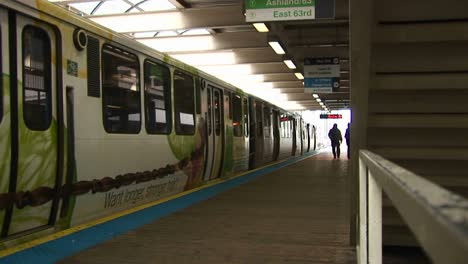 Passengers-Exit-A-Colorful-Commuter-Train-Before-It-Departs-As-Another-Train-Arrives-At-The-Station