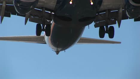 An-Airplane-Flies-Over-Power-Lines-With-Its-Landing-Gear-Down-In-Preparation-For-Landing
