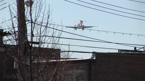 A-Lowflying-Airplane-Passes-Over-Power-Lines-And-The-Inner-City