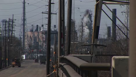 An-Innercity-Industrial-Area-With-Refineries-Utility-Wires-Smoke-And-Traffic