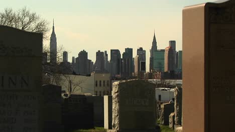 The-New-York-City-Skyline-Is-Framed-Between-Two-Headstones-In-A-Brooklyn-Cemetery