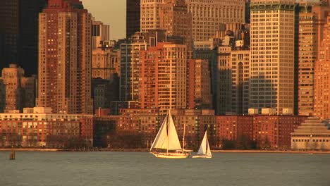 Sailboats-Pass-Each-Other-On-A-Bright-Sailing-Day-With-Manhattan-In-The-Background