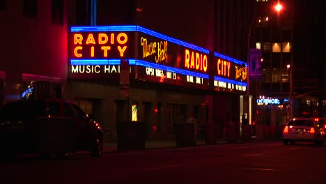Cars-Pass-By-The-Brightly-Lit-Radio-City-Musical-Hall-Marquee-At-Night