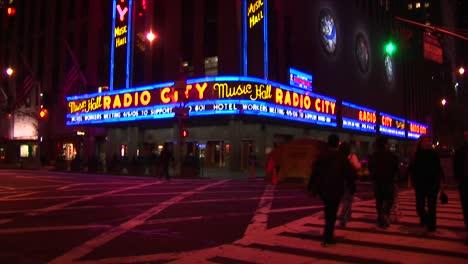 Radio-City-Music-Hall-At-Night-With-Lights-Traffic-And-Pedestrians