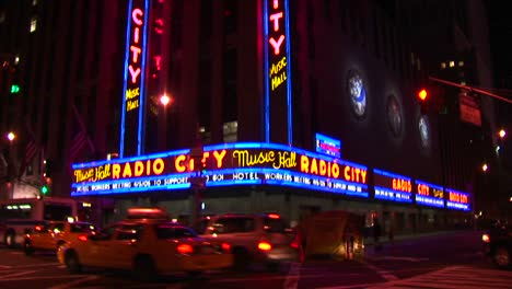 The-Camera-Pans-Down-The-Radio-City-Music-Hall-Signs-And-Marquee-To-Street-Level-With-Taxis-And-Pedestrians-In-A-Night-Shot