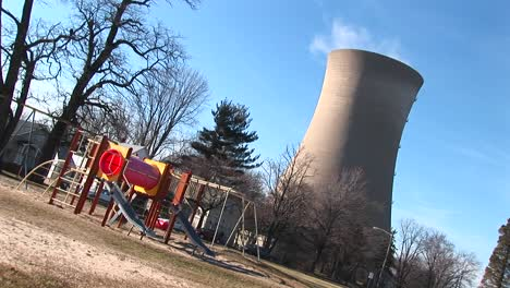 The-Camera-Tilts-To-Show-A-Playground-And-Nuclearpower-Plant-Near-Each-Other