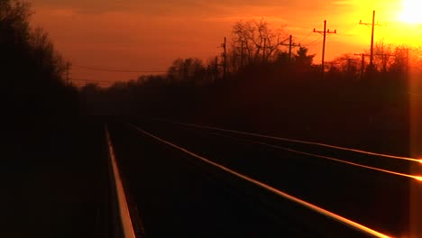 A-Brilliant-Goldenhour-Sky-Casts-Its-Reflection-On-Railroad-Tracks-Stretching-Towards-The-Horizon