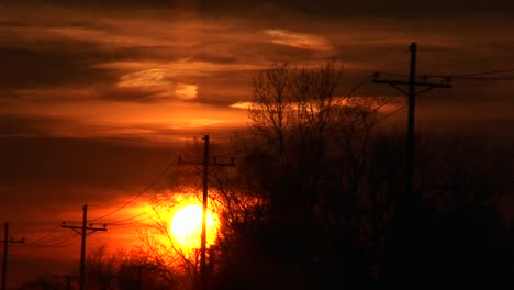 A-Colorful-Sunset-With-Powerlines-And-Silhouetted-Trees