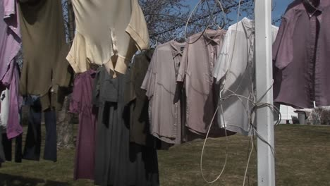 Colorful-Shirts-And-Dark-Dresses-Hand-On-A-Clothesline-To-Dry-Near-A-Large-Country-Home