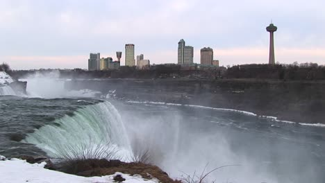 The-Tourist-Hotels-And-Viewing-Tower-Look-Stark-Against-A-Pale-Sky-With-Niagara-Falls-In-The-Foreground