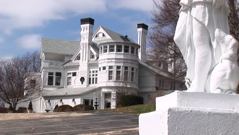 The-Camera-Focuses-On-A-Giant-White-Ornate-Mansion-Designed-With-Many-Different-Winds-And-Architectural-Elements