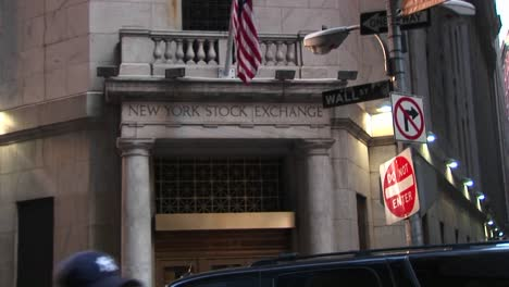 The-Camera-Pans-Up-From-The-Bronze-Door-Entrance-Of-The-New-York-Stock-Exchange-To-The-American-Flag-And-The-Wall-Street-Sign